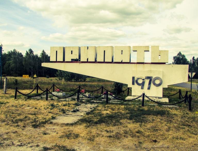 Skiltet som viser hvor Pripyat by ligger. Legg merke til skiltene som advarer mot radioaktivitet. På den ene skiltet står det