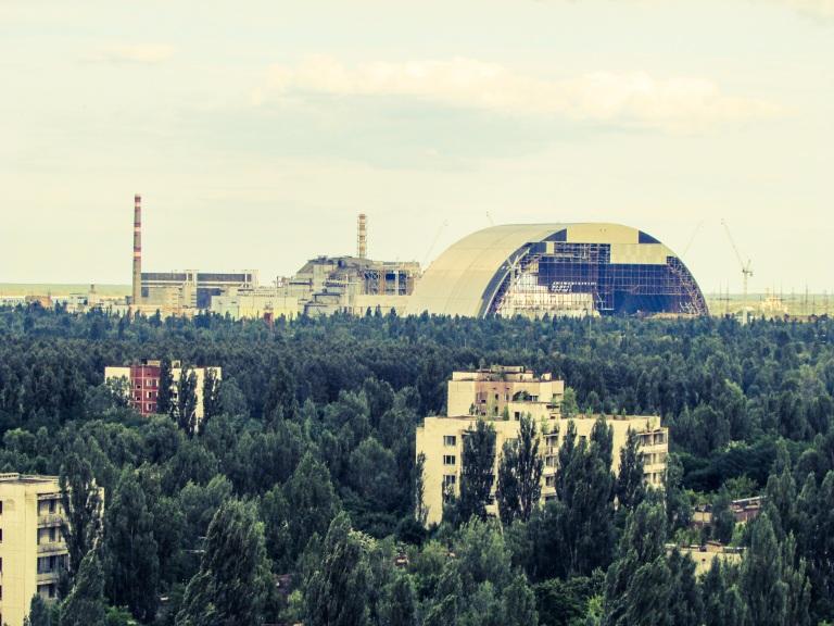 Fra taket av en Pripyats høyeste bygninger ser man utover byen, mens reaktor nummer tre og fire sees litt lenger unna.  Ved siden av reaktorene den nye