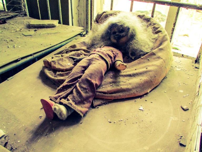 En dukke ligger forlatt på en seng på en av sovesalene.