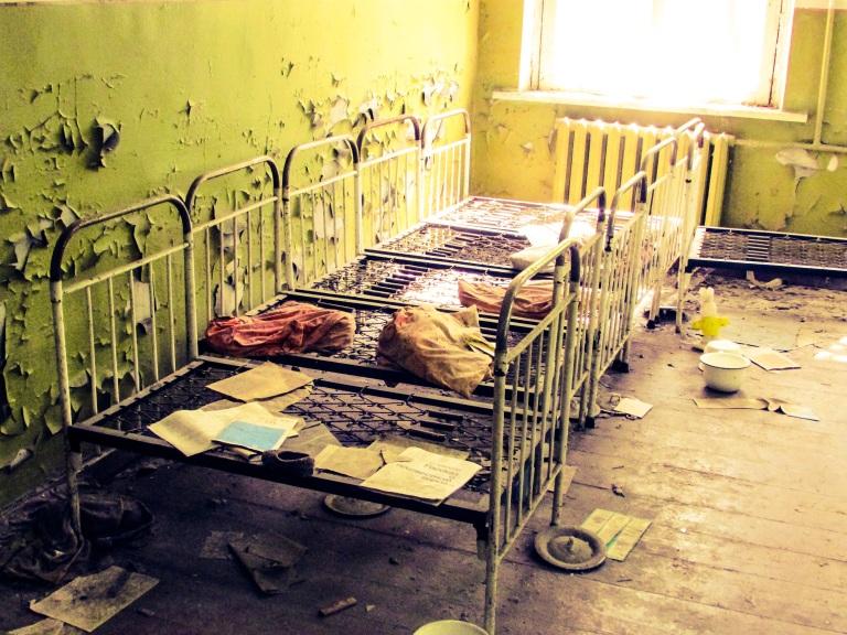 På rekke og rad står sengene inne på det som var en av sovesalene.